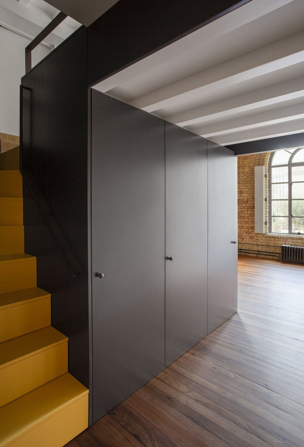 The yellow stairs lead to the apartment's upper level